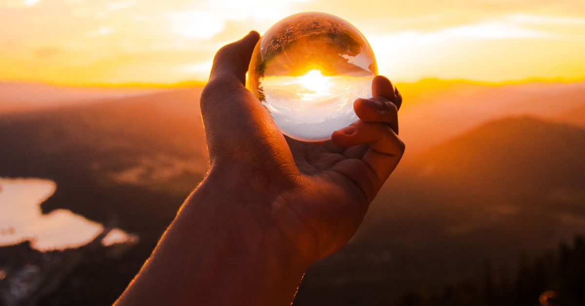 a glass ball in front of the sunset